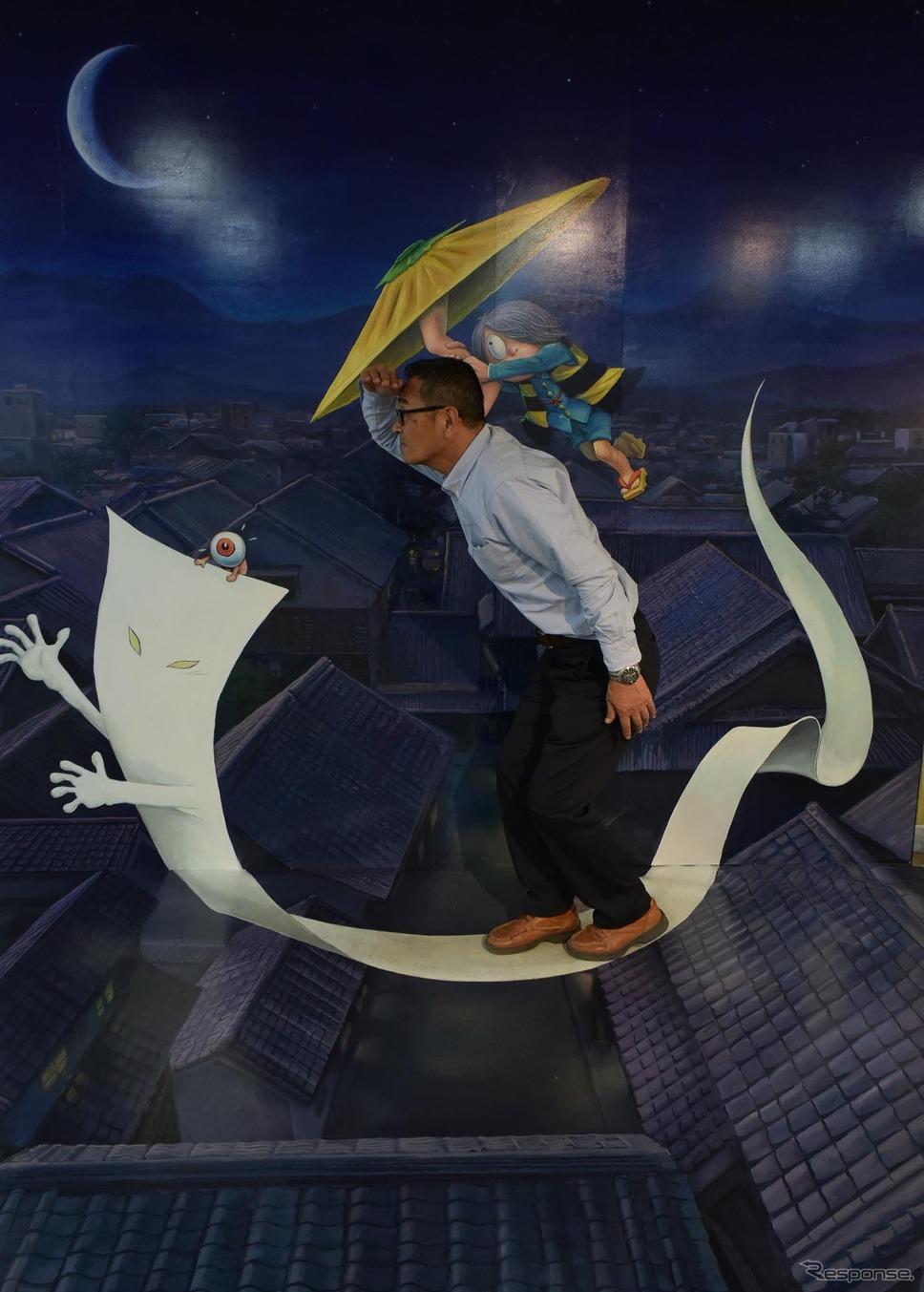 記念撮影コーナー。鹿児島・大隅半島南部に伝承のある妖怪、一反木綿に乗って空を飛ぶイメージ。乗っているのは庄司館長。《撮影 井元康一郎》