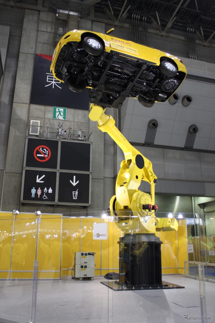 高々とカローラフィールダーを持ち上げ、さらに傾けて底面を見せつけるFANUC Robot M-2000iA/1700L。