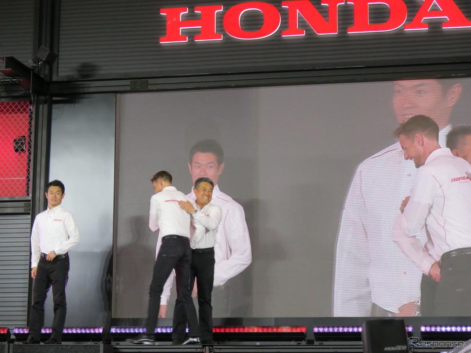 バトンと軽く抱擁する山本部長(左端はバトンの僚友ドライバー・山本尚貴)。《撮影 遠藤俊幸》