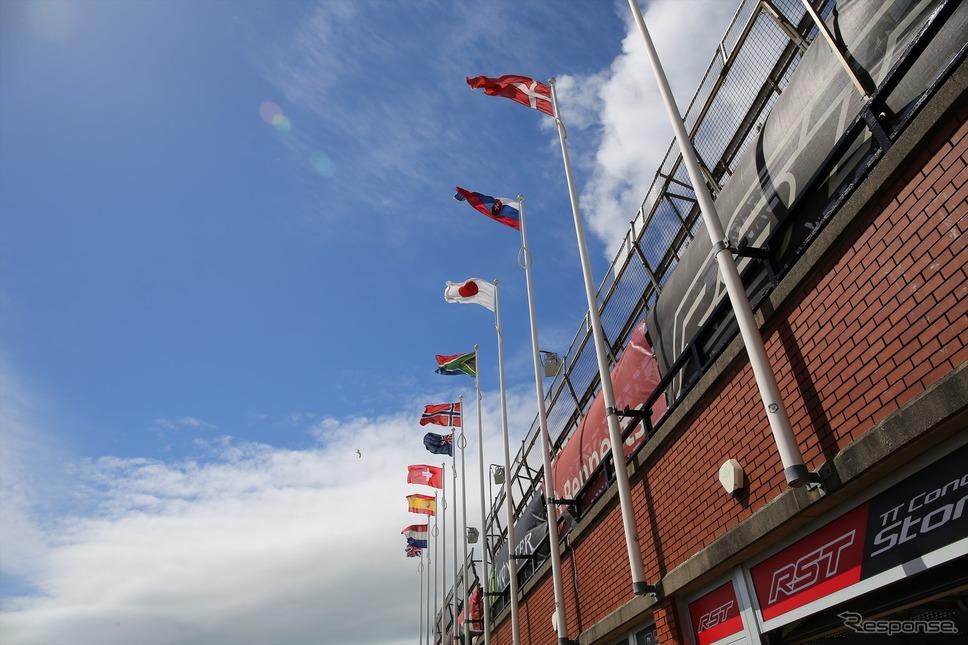 グランドスタンドに掲揚されている国旗は参加選手の国籍が反映されていて日章旗もある(マン島TTレース2019)《撮影 小林ゆき》