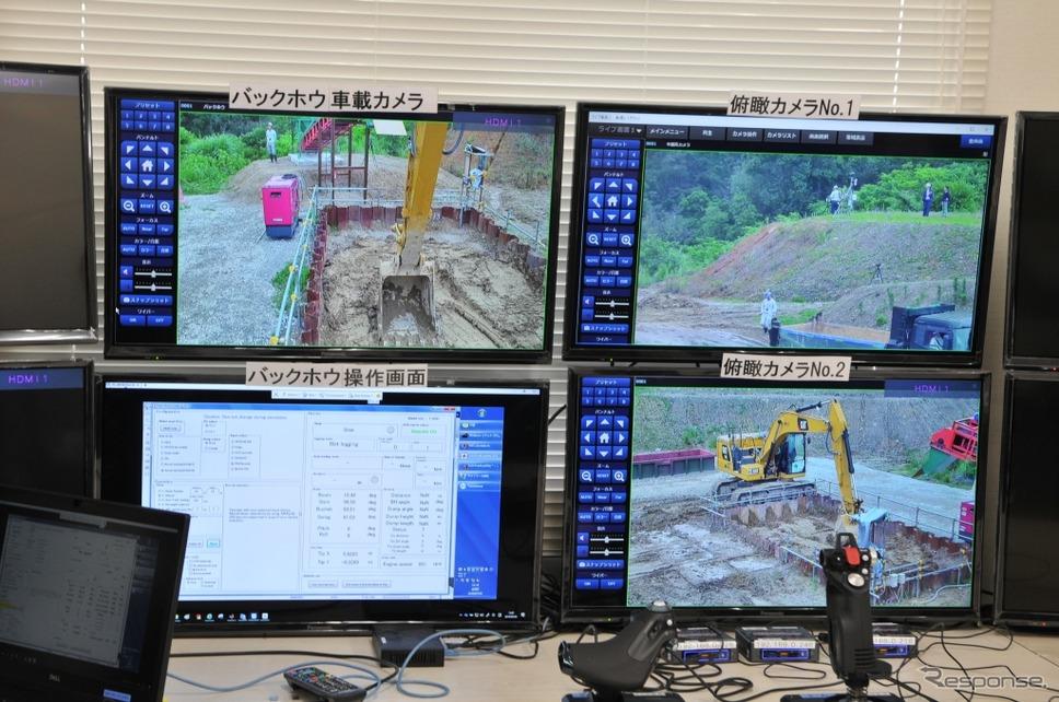 遠隔操作室には監視用カメラのモニター3つ、そして機体・作業情報を表示するモニターおよび各種コントローラーがある。《写真 丹羽圭》