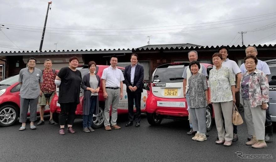 コミュニティ・カーシェアリングへのタイヤ寄贈セレモニーに参加した日本カーシェアリング協会の吉澤武彦代表理事(中央左)、横浜ゴムの森智朗CSR本部長代理(中央)とコミュニティ・カーシェアリングを利用する石巻市の人たち《画像:横浜ゴム》