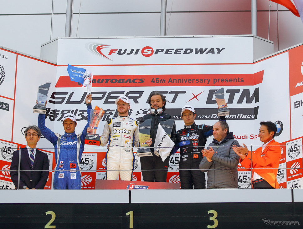 レース1の表彰式。左2人目から右へ、2位の塚越、優勝のキャシディと山田淳監督、3位の山本、DTM側の統括団体代表で往年の著名F1ドライバーでもあるゲルハルト・ベルガー。《撮影 益田和久》
