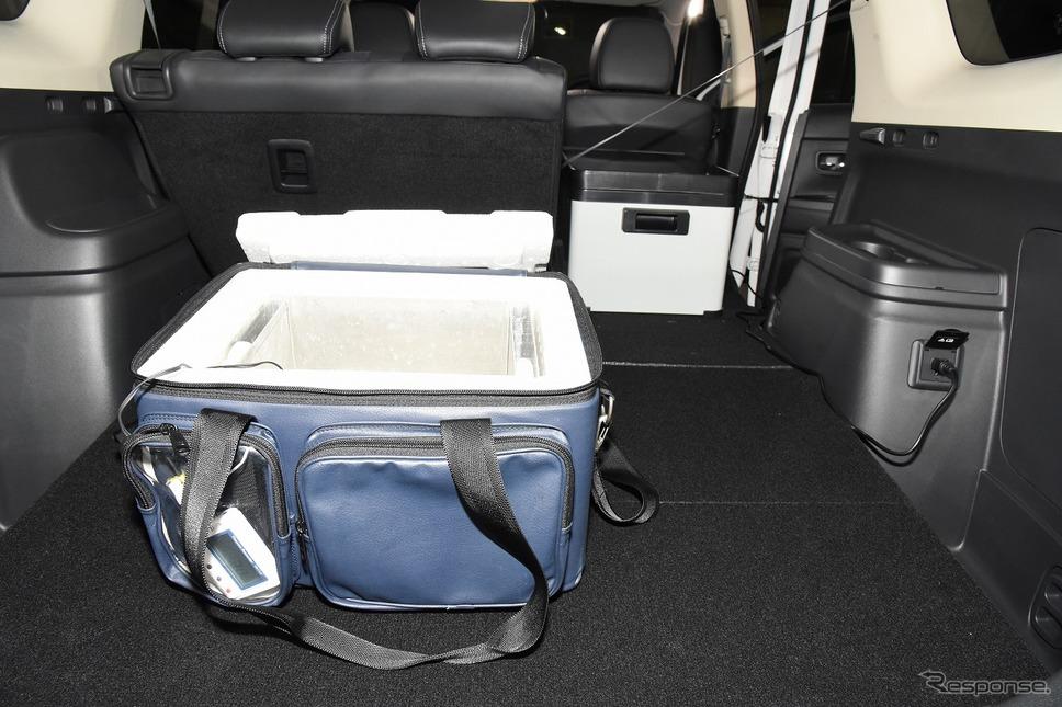 ワクチンを輸送するための保冷バッグ。右奥はアウトランダーPHEVから給電している冷凍庫《写真提供 三菱自動車工業》