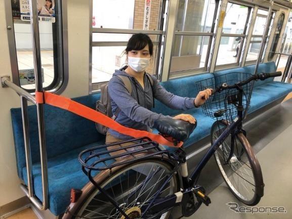 車内には固定具がないため、このように固定ベルトを使い、自転車を自分で支える。《写真提供 西武鉄道》