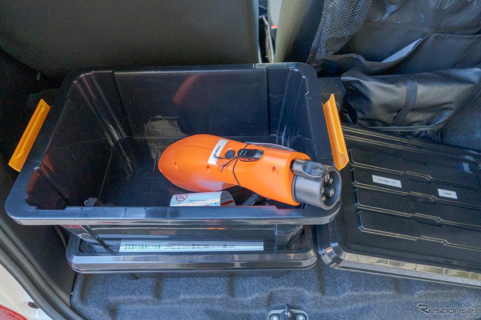 ヴィークルパワーコネクター。オレンジ色の部分のなかにコンセントが用意されている。充電ポートに接続し、白いシールが貼られた部分にある丸いボタンを押せば車のバッテリーの電力が外部に供給される。《写真撮影 関口敬文》